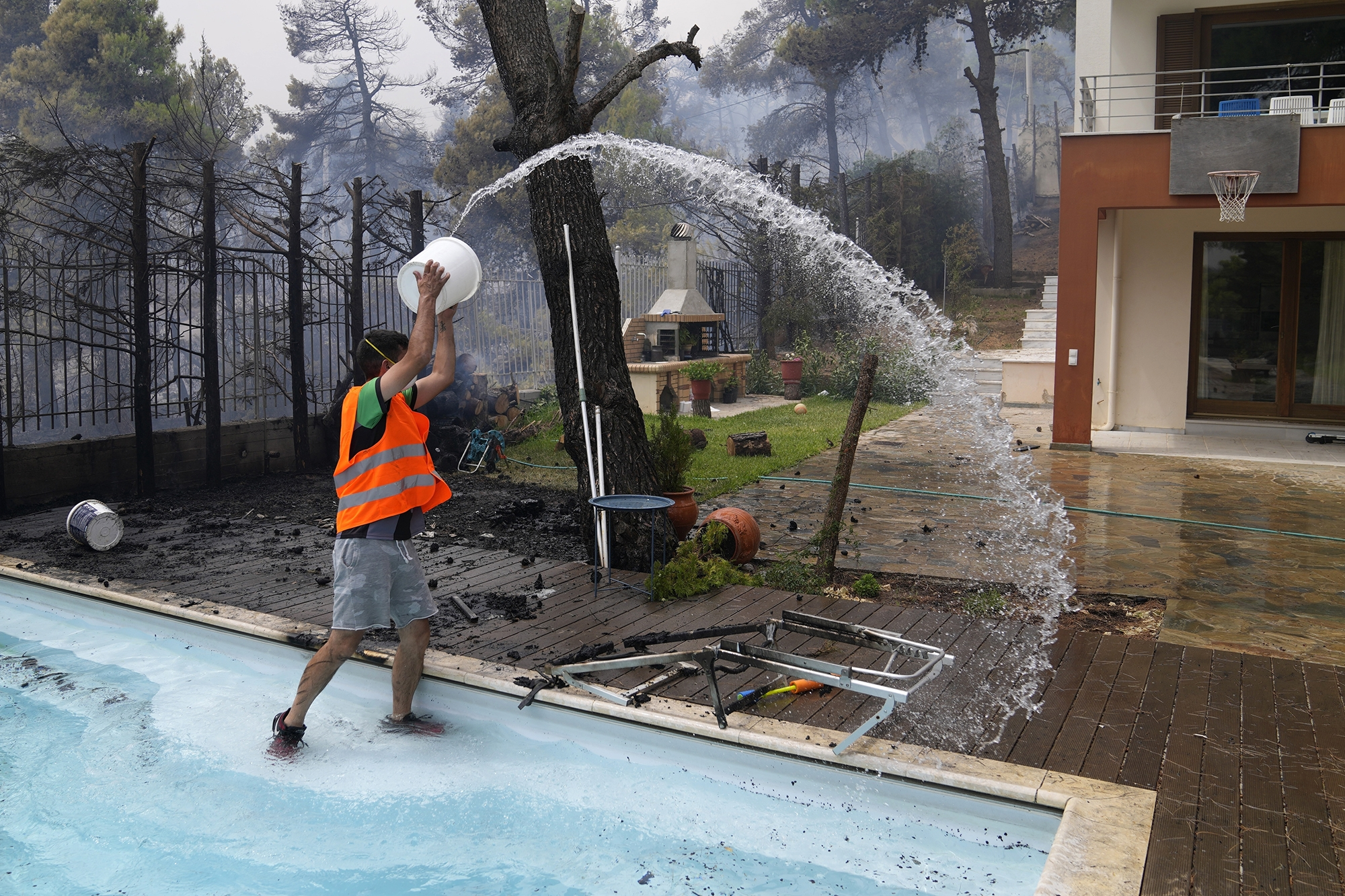 A man throws water from a swimming pool as fire approaches his house near Athens, Greece, on Friday.