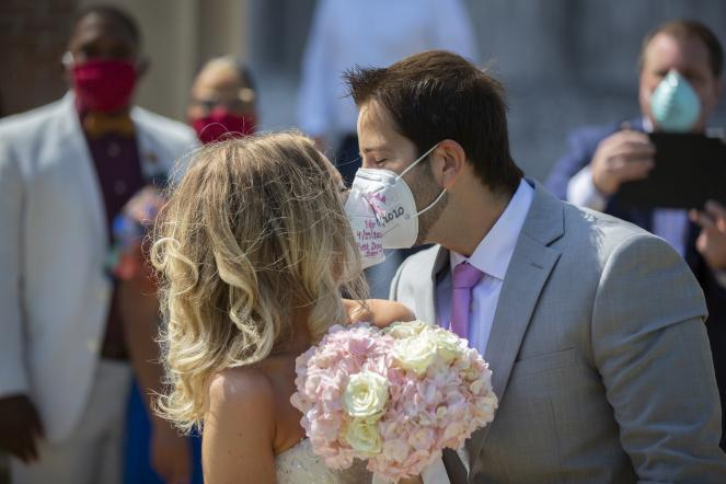 Gabrielle Schmees, 29, and Diego Grassano, 31, kiss wearing protective masks on the day of their wedding at the Gerald D. Hines Waterwall Park on Monday, April 27, in Houston.