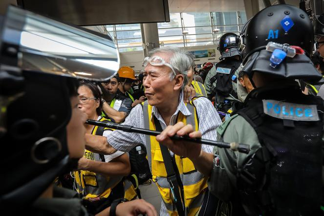 "Protect the Children volunteer ""Uncle Wong"" shields protesters from the police, along with other ""silver hair"" volunteers in the Tung Chung district in Hong Kong during 2019 demonstrations."