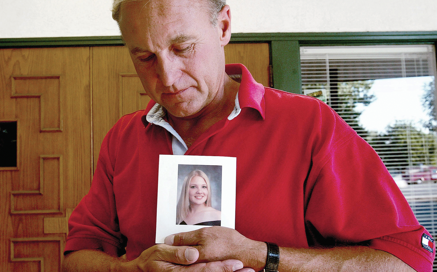 Monty Patterson holds a photo of his daughter, Holly, who died after taking RU-486.