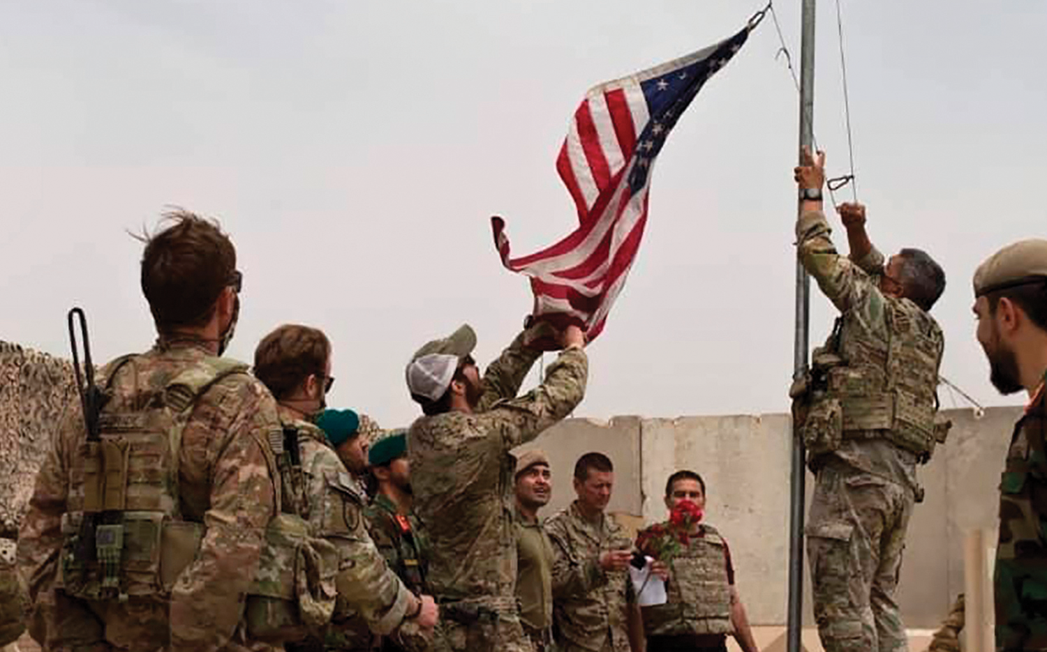 U.S. soldiers lower an American flag at a handover ceremony at Camp Antonik.