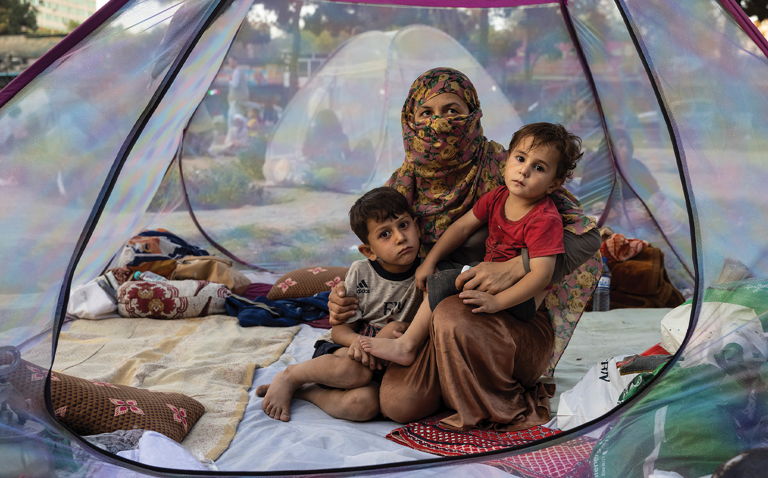 A woman who lost her husband a week earlier to the Taliban shares a tent with her children at a makeshift camp for displaced persons in Kabul.