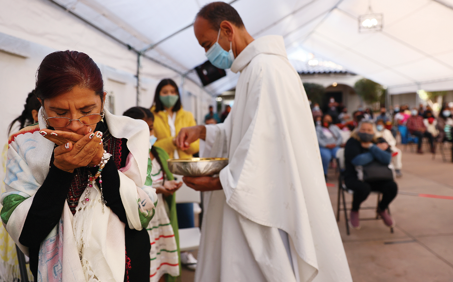 The Rev. Arturo Corral distributes Communion during an outdoor Mass at the historic Our Lady Queen of Angels Church in Los Angeles.