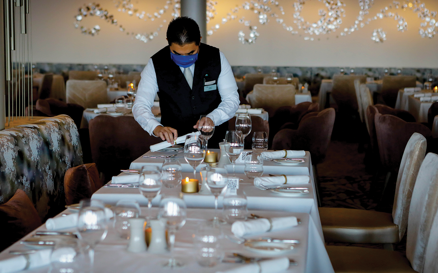 An employee sets a table at the Cosmopolitan Restaurant on the Celebrity Edge cruise ship, the first revenue-earning cruise to depart from the U.S. after the pandemic-induced hiatus.
