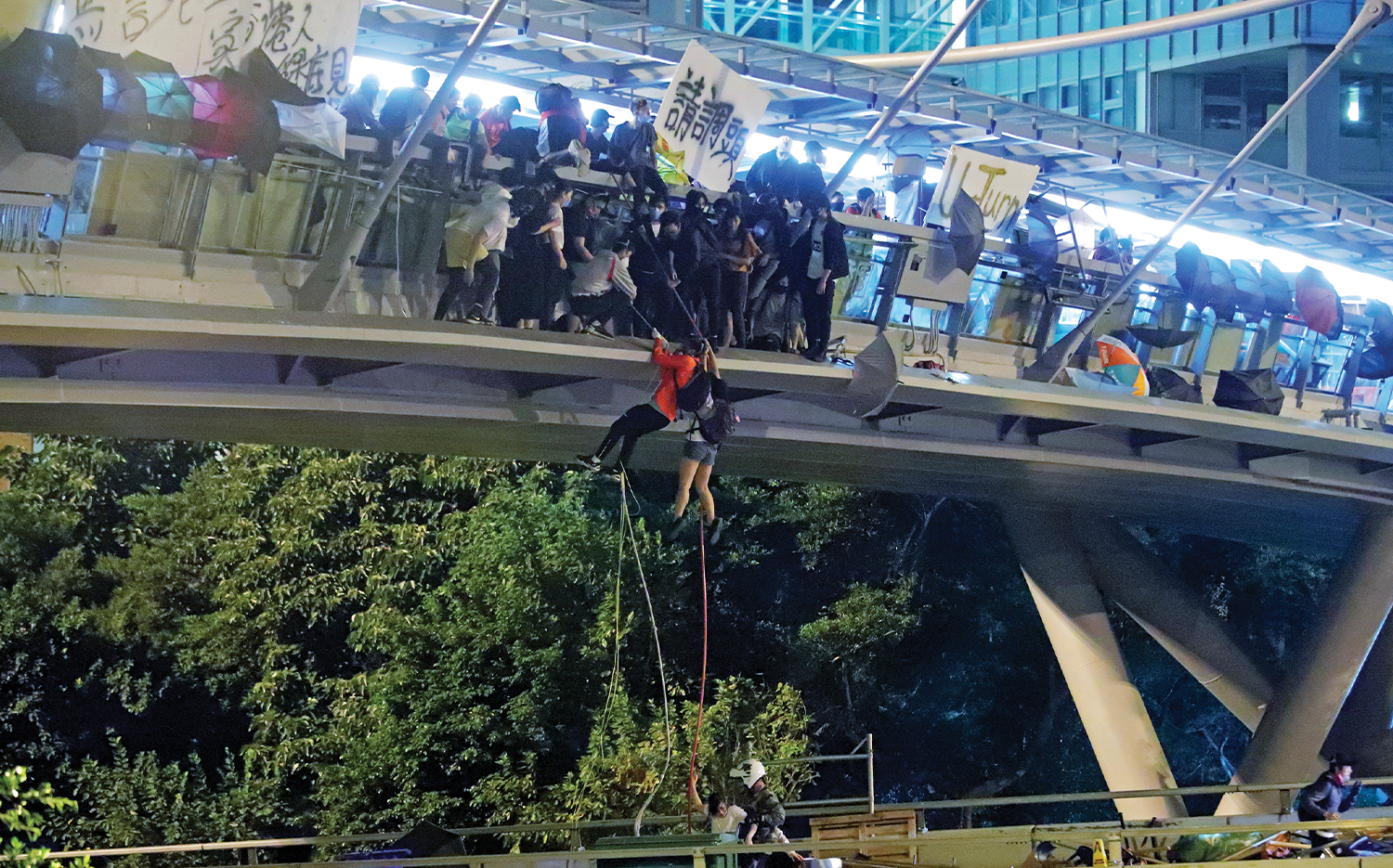 During the 2019 siege at PolyU, protesters use ropes to lower themselves from a pedestrian bridge to waiting motorbikes in order to escape.