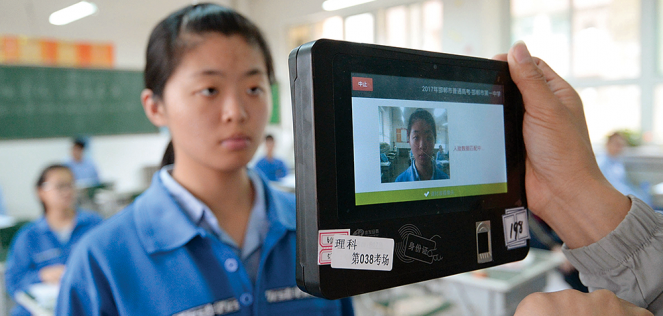 A teacher uses a machine that employs both fingerprint and facial recognition technology to check the identification of a student before an exam in Handan in China's Hebei province.