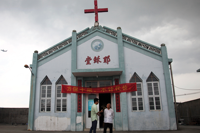 """Wuxi Christian Church in 2014, with the words """"Church of Jesus"""" in red, in Zhejiang province."""