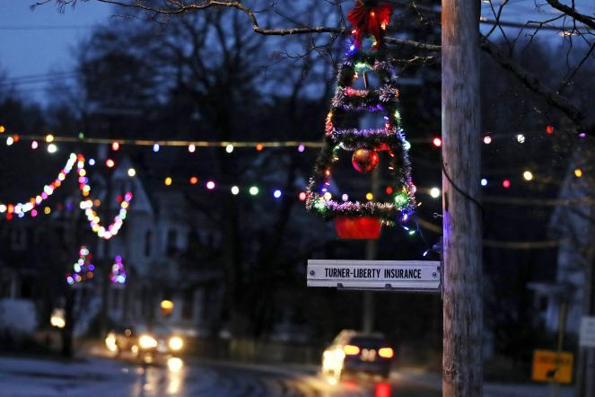 A lit Christmas tree hangs from a pole at dusk as holiday lights illuminate downtown in Farmington, N.H. As the coronavirus spreads, holiday lights are going back up to provide a bit of emotional and actual brightness.