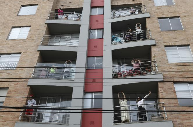 Residents take part in an aerobics class led by city police instructing from the street below during a lockdown ordered by the government in an effort to prevent the spread of the new coronavirus, in Bogota, Colombia.
