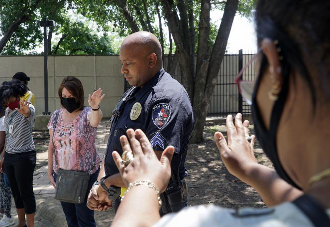 Arlington Police Sgt. Jeremy Lee was among several officers at a prayer for peace at police headquarters in Arlington, Texas, on Tuesday.