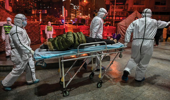 Medical staff members arrive with a patient at the Red Cross Hospital in Wuhan.