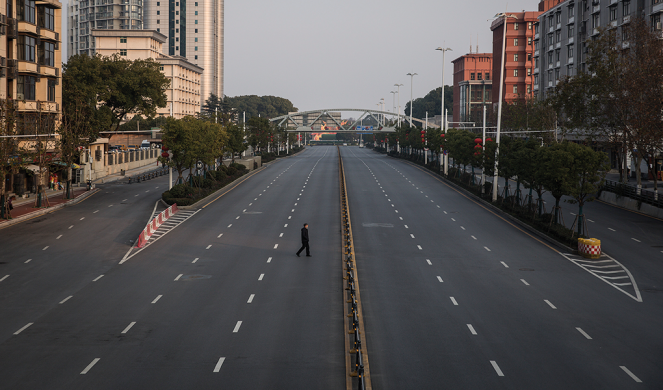 A man crosses an empty highway in Wuhan.