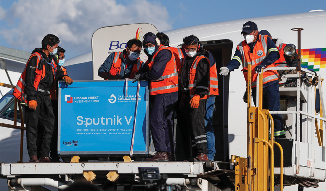 Airport employees unload the first shipment of Russia's Sputnik V COVID-19 vaccine after it arrived in Bolivia.