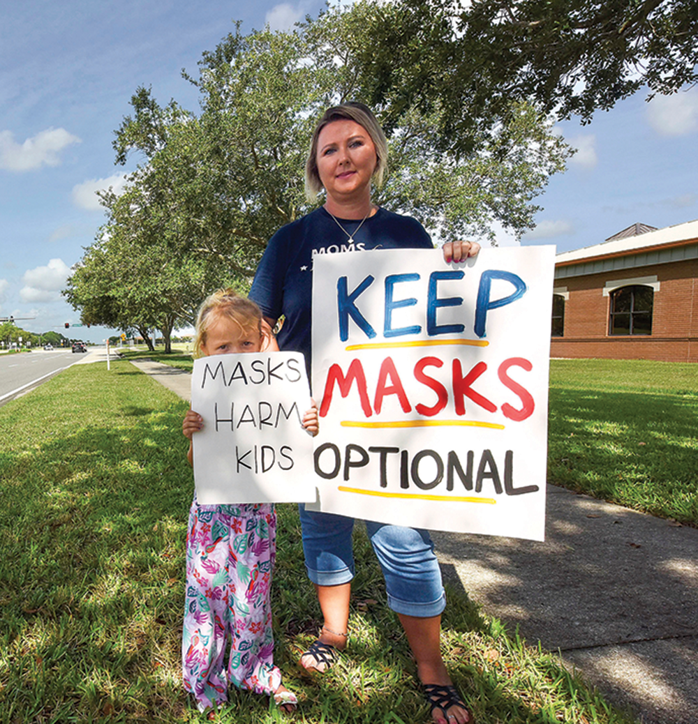 People demonstrate with placards outside an emergency meeting of the Brevard County School Board in Viera, Fla.