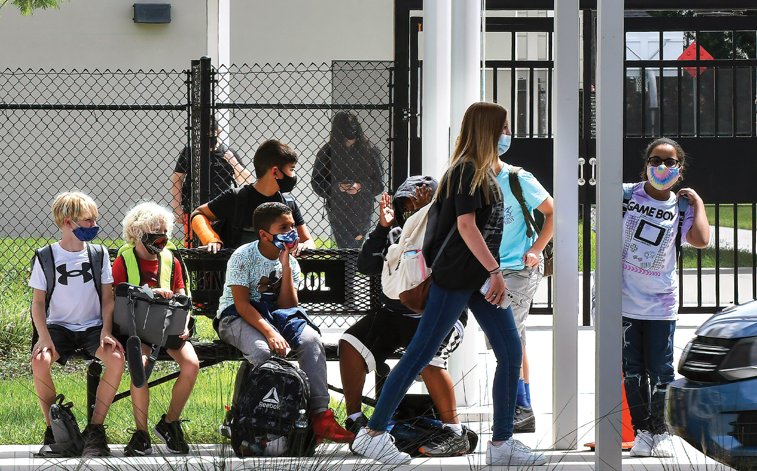 Students wearing face masks wait to be picked up by their parents at Pershing School in Orlando.