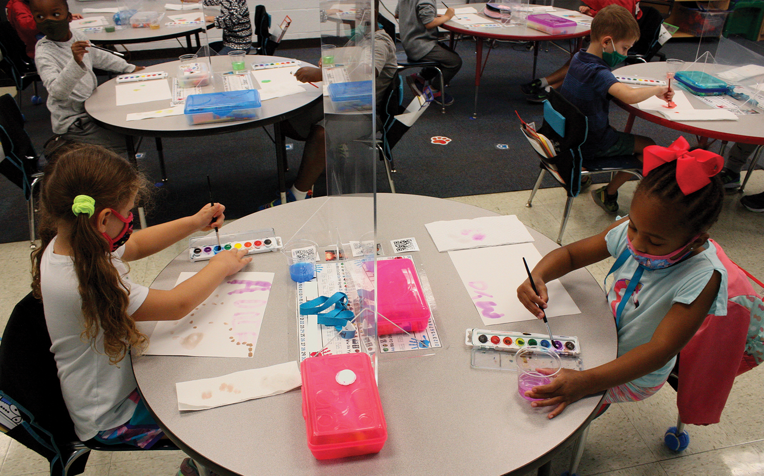 Plexiglass shields protect kindergartners at Central Christian School, providing workspace for two students at tables rather than the typical number of four.