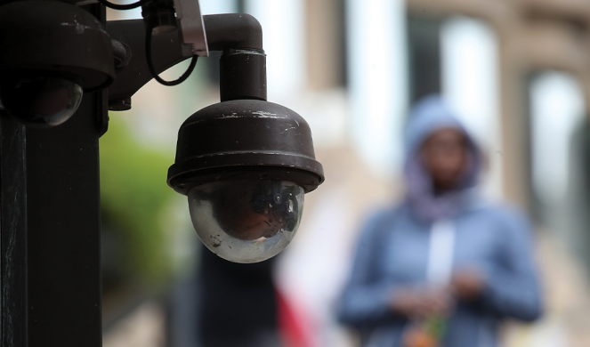 A video surveillance camera hangs from the side of a building in San Francisco, Calif.