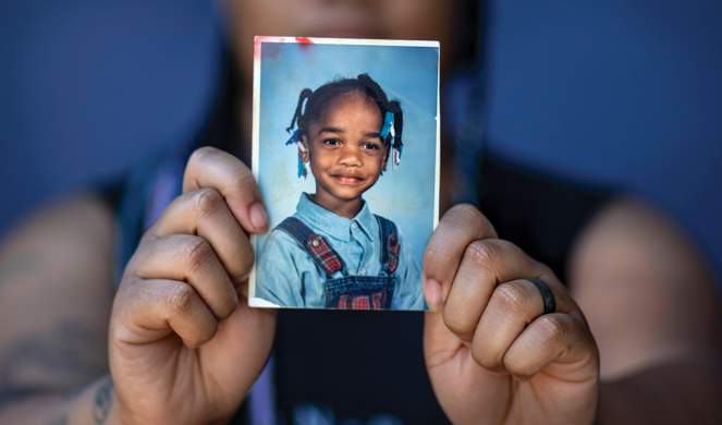 Keanakay Scott holds a photo of herself when she was a child.