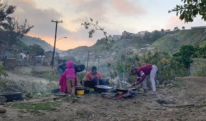 Haitians cook dinner.