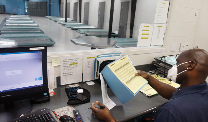 Alfred Jones has a view of the client area at Houston Recovery Center as he processes paperwork in the office.