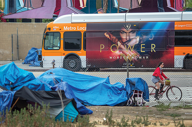 A bus passes homeless encampments in Los Angeles.