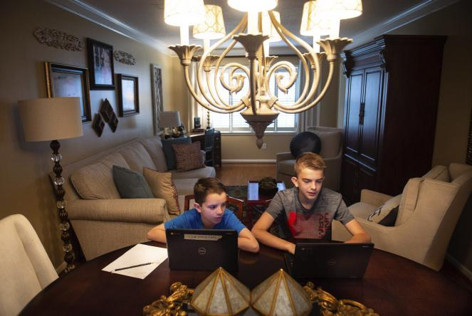 Brothers John Evan, 9, left, an elementary student, and Mason Sinclair, 12, a middle school student, extend their learning with virtual projects on their Chromebooks at their home.