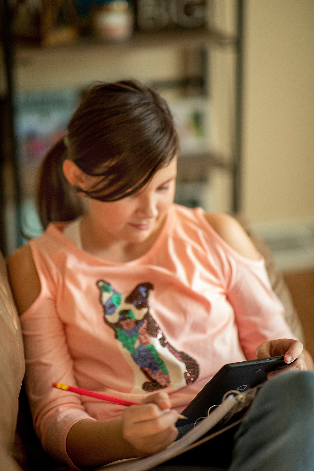 Using a tablet, Hannah Davis does her history homework from the couch.