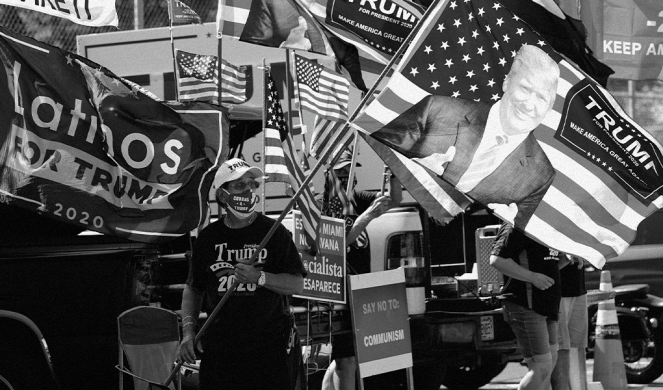 Orlando Bacallao waves a banner outside an early voting location last October in Hialeah, Fla.