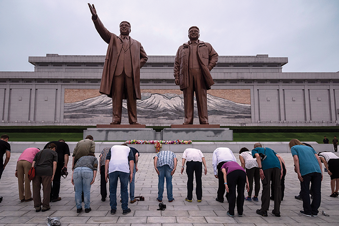 A group of tourists bow (on command from their tour guide) before statues of late North Korean leaders Kim Il Sung (left) and Kim Jong Il (right) in Pyongyang.