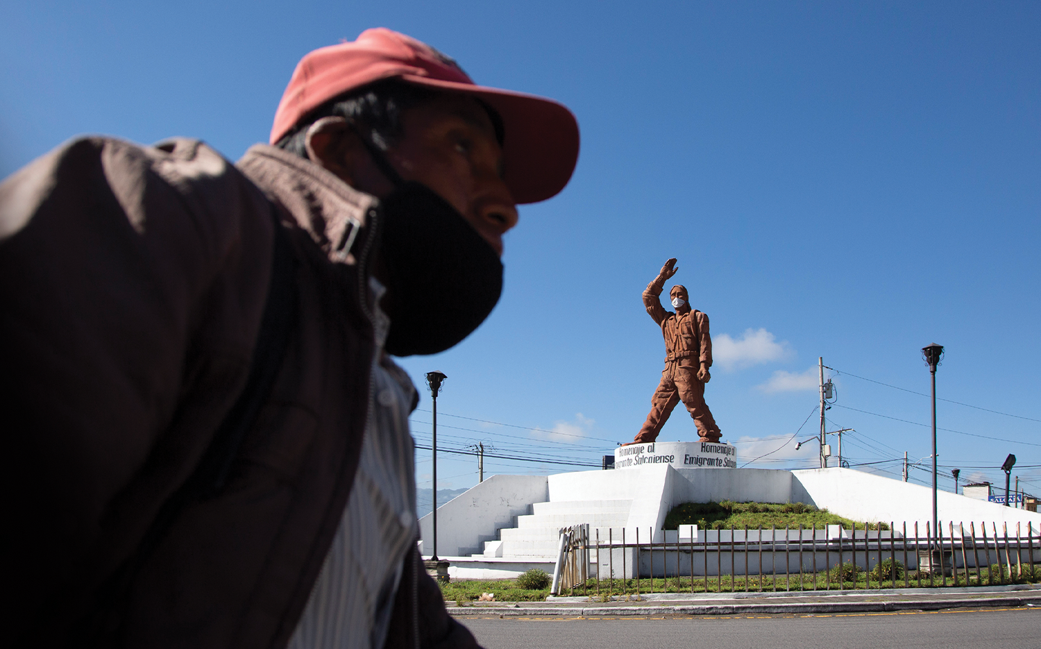 A man walks near a monument that pays homage to migrants at the entrance to the town of Salcajá.