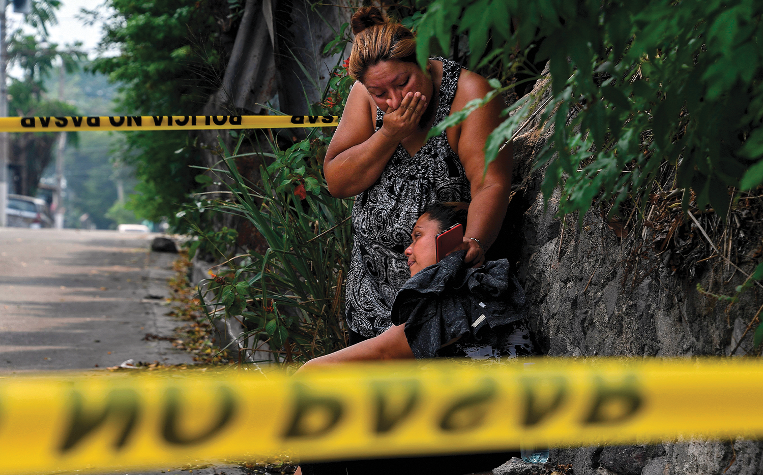 Relatives of a man shot dead in Ayutuxtepeque, El Salvador, cry near the crime scene.