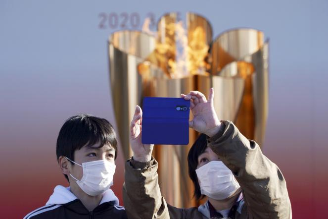 """Two visitors take a selfie with the Olympic """"Flame of Recovery"""" burning during its display ceremony Wednesday. IOC President Thomas Bach has agreed to a proposal of postponing the Tokyo Olympics for about one year until 2021 because of the coronavirus outbreak, Japanese Prime Minister Shinzo Abe said Tuesday."""