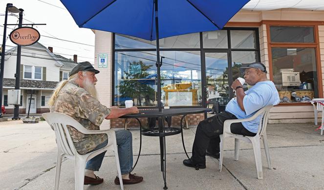 Eddie Scheckler (left) talks over coffee with friend Bill Epps outside the café.