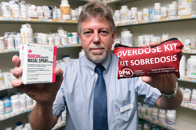 A Connecticut pharmacist holds Narcan and an overdose kit.