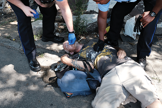 Police administer Narcan as they try to revive a man who overdosed on heroin in Philadelphia (the man later came to and was taken to the hospital).