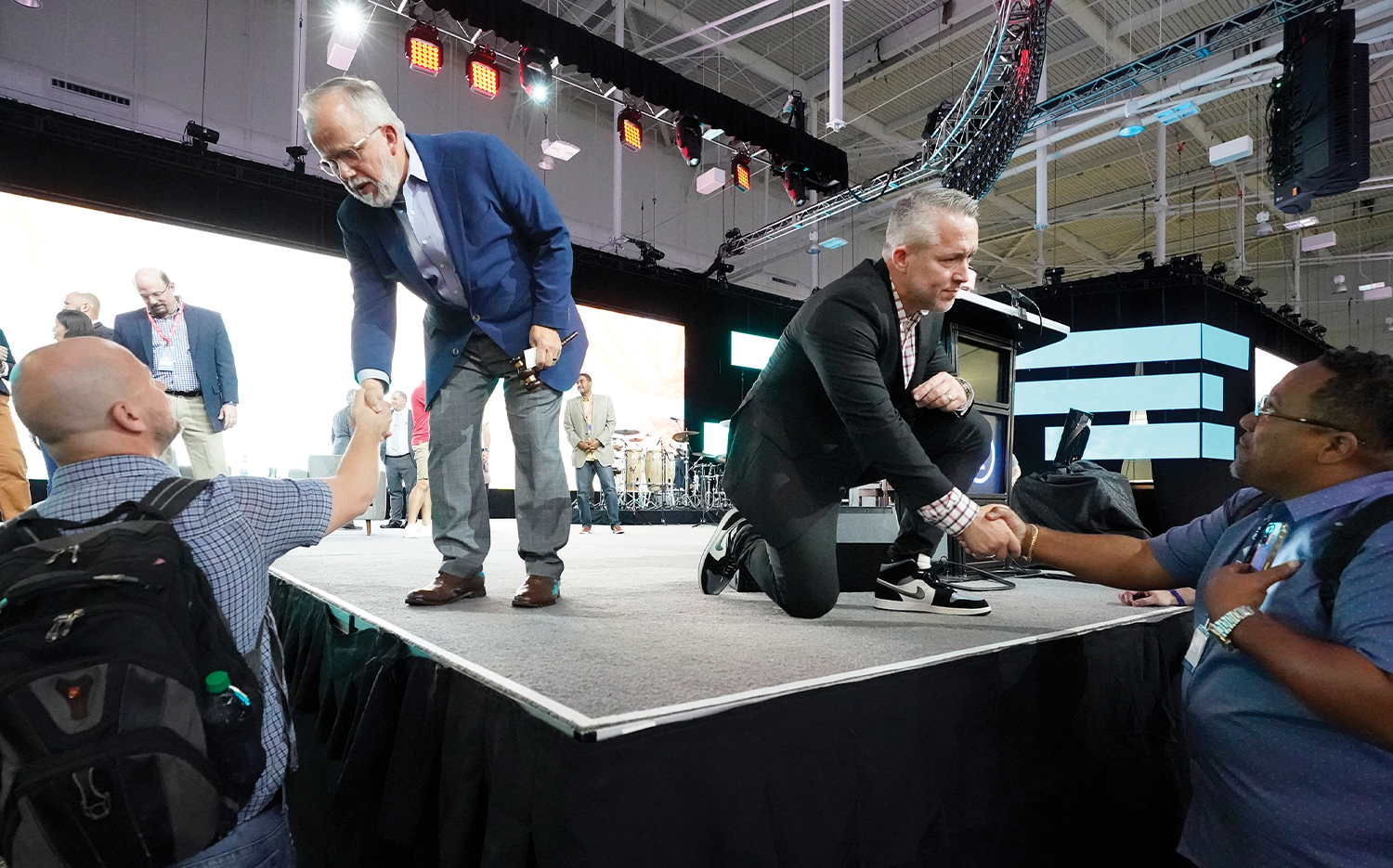 Incoming Southern Baptist Convention President Ed Litton (standing at left) and outgoing President J.D. Greear (kneeling at right) talk with denomination members at the conclusion of the annual Southern Baptist Convention on June 16.