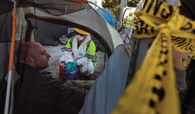An LA city worker talks to a man living in a tent on a sidewalk along Cherokee Avenue.