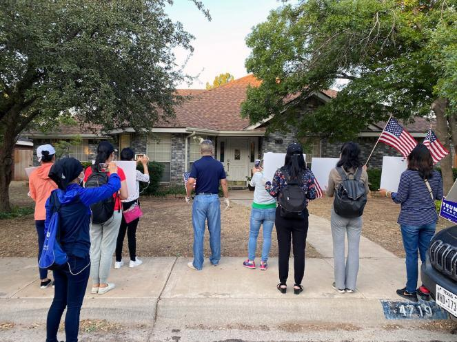 Protesters stand outside the home of Bob Fu.