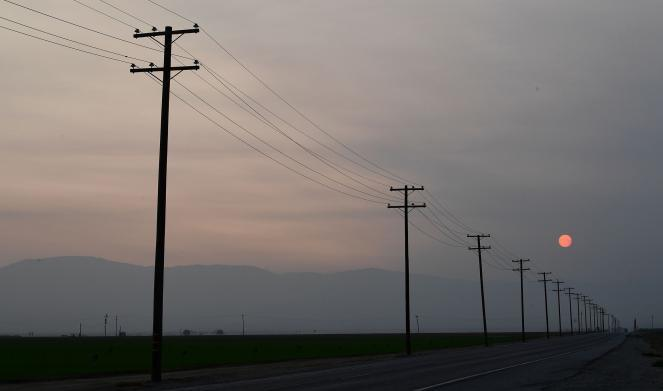 The sun rises over the smoke-filled California sky over Kern County, California.