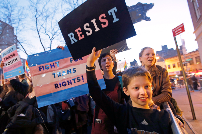 Tal Moskowitz, 8, a transgender child, attends a rally in support of transgender youth with parents Faigy Gelbstein (left) and Naomi Moskowitz (upper right) in New York.