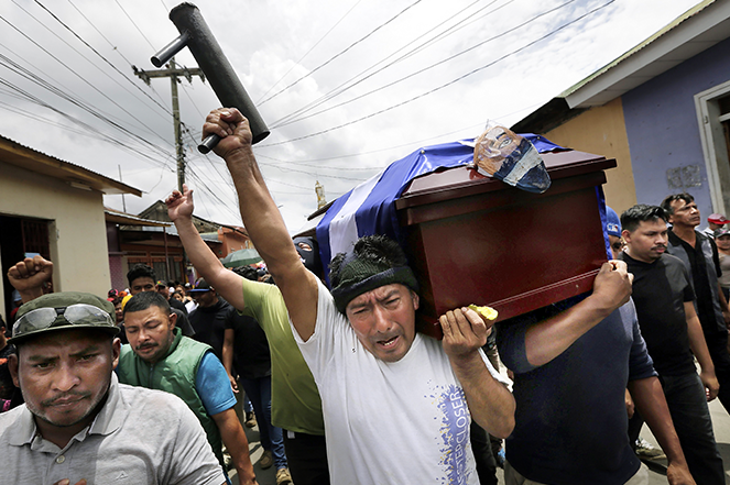 A mourner carries a homemade mortar and shouts anti-government slogans as he carries the casket of a protester who was shot dead during protests against the government in Managua, Nicaragua.