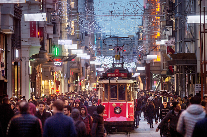 Shoppers crowd into a busy street alongside the Taksim-Tunnel Nostalgic Tramway in Istanbul.