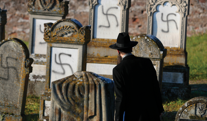Rabbi Harold Abraham Weill examines vandalized tombs in the Jewish cemetery of Westhoffen, west of Strasbourg, France.
