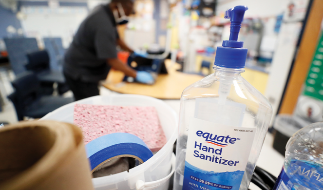 Hand sanitizer sits on a cart as a custodian cleans a classroom.