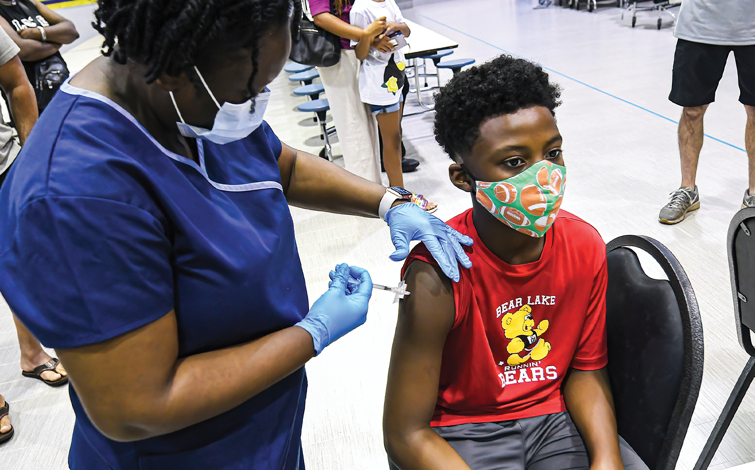 A nurse gives a dose of the Pfizer vaccine to a 12-year-old boy at a COVID-19 vaccine clinic at Lyman High School in Longwood, Fla., on the day before classes began in August.