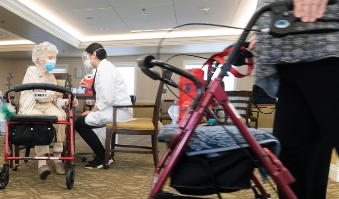 A pharmacist intern talks with a resident at a senior living community in Anaheim, Calif., after giving the COVID-19 vaccine.