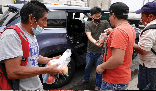 Pastor Greg Woo (in dark gray shirt) delivers snack items to day laborers.